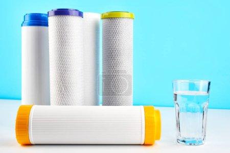 Photo pour Filtres à eau. Cartouches de carbone et un verre sur fond bleu et blanc. Système de filtration domestique. - image libre de droit