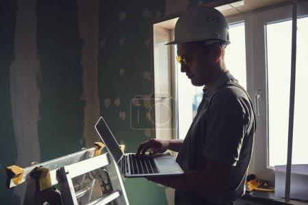 Foto de Servicio de habitación. Constructor en un casco y gafas se encuentra en el perfil con un ordenador portátil en la mano en el fondo de la obra - Imagen libre de derechos