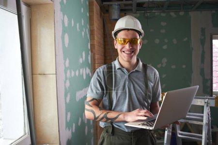Foto de Servicio de habitación. Sonriente joven constructor en casco y gafas está parado con un ordenador portátil en la mano contra el fondo de una obra de construcción - Imagen libre de derechos
