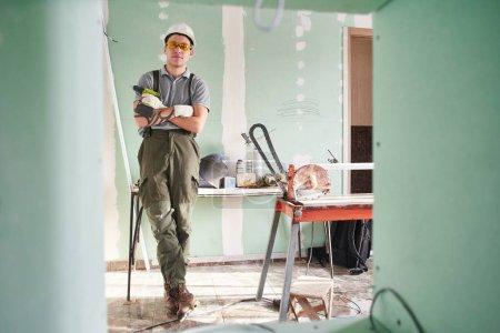 Foto de Servicio de habitación. Constructor de joven en un casco y el mono de pie con los brazos cruzados en el fondo de la obra - Imagen libre de derechos