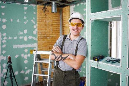 Foto de Jóvenes sonriente constructor en casco y el mono de pie con los brazos cruzados en el fondo de la obra, concepto de la reparación de la sala - Imagen libre de derechos