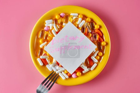 Photo for Concept of alternative medicine. Vitamins in capsules, nutrients, tablets and pills in a yellow plate with a fork on a pink background. Inscription Dietary Supplements on the sticker - Royalty Free Image