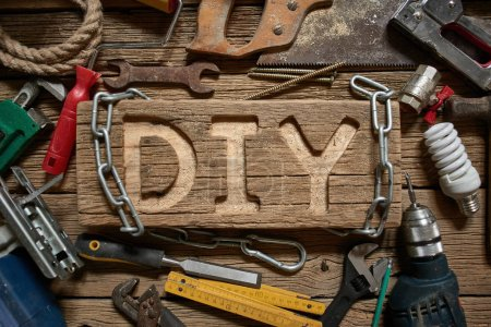 Photo for DIY letters on a wooden board on the background of working tools. Do It Yourself concept. - Royalty Free Image
