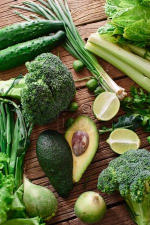 Photo for Fresh green vegetables and fruits and greens on a wooden background. Healthy eating concept - Royalty Free Image