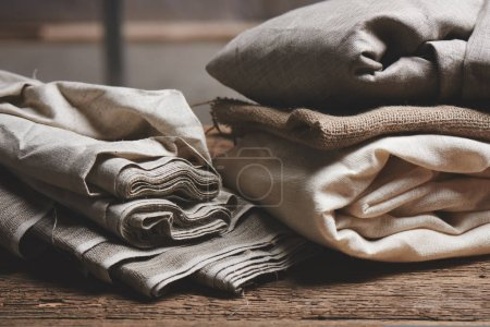 Foto de Natural fabrics from organic colors of flax and cotton in rolls, homespun textile handmade. Burlap and canvas for eco, rustic, boho, hygge decor - Imagen libre de derechos