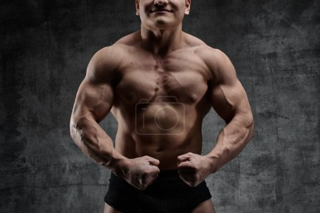Photo for Sexy bodybuilder man posing on dark background in black shorts. Handsome pumped male body isolated with free space for advertising - Royalty Free Image