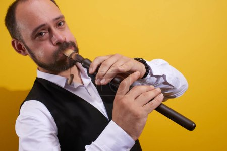 Photo for Professional musician man playing a pipe closeup in a yellow studio. Folk wind instrument, flute - Royalty Free Image