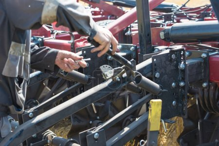 One worker with adjustable wrench repairing one engine