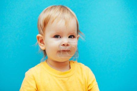 Photo pour Adorable petit enfant en t-shirt jaune regardant caméra isolée sur bleu - image libre de droit