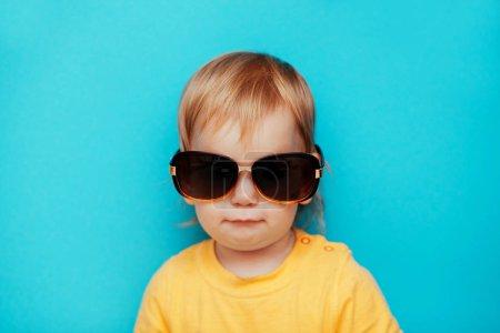 Photo pour Petite fille à la mode dans des lunettes de soleil debout isolé sur fond bleu - image libre de droit