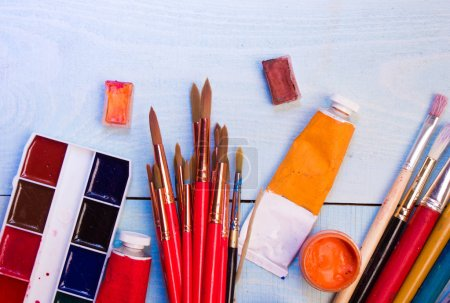 Paints, brushes on the wood background. The workplace of the artist. Banner for school.