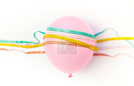Idea of weight loss. Balloon with measuring tapes