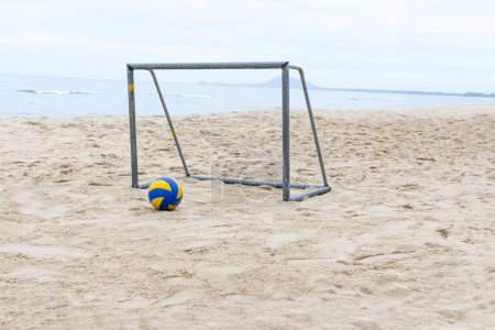 Blue and Yellow volleyball and goalpost on beach for playing football for summer sport