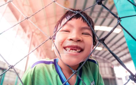 Photo for Happy asian kid with smile in a soccer training field for children sport recreation lifestyle concept. - Royalty Free Image