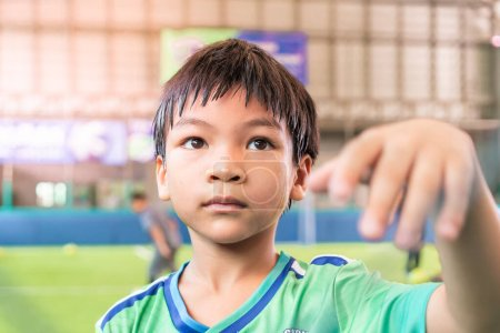 Photo for Portrait of an asian boy in Soccer uniform in an indoor soccer training pitch. - Royalty Free Image