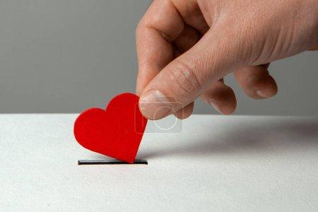 Photo pour Main de l'homme place coeur dans la fente de don. Le concept du donneur de sang ou d'organes humains, sauver des vies. - image libre de droit