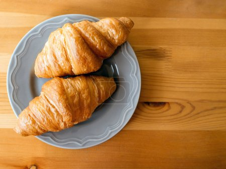 Photo for Fresh baked croissants on a wooden background - Royalty Free Image