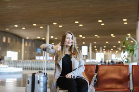 Happy woman sitting in airport hall with modern tablet near valise and showing thumbs up.