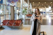 """Постер, картина, фотообои """"Female person going in airport hall with valise and using smartphone."""""""