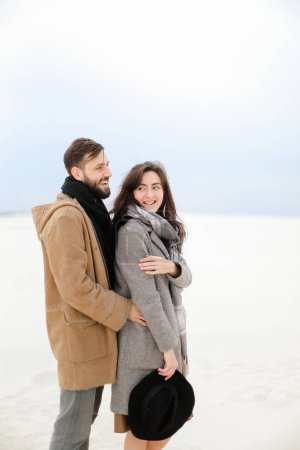 Happy man with beard hugging female person wearing grey coat and scarf, white winter monophonic background.