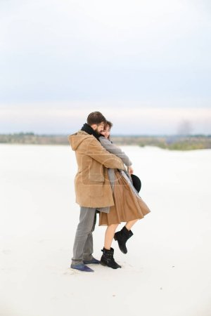 European man hugging woman in snow winter background, wearing coat and scarf.