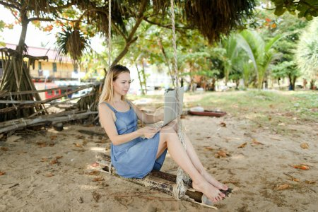 Young blonde girl using laptop and riding on swing on sand.