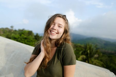 Young smiling woman standing in mountains background, wearing khaki shirt.