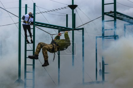 Photo for Uzhgorod, Ukraine - October 14, 2020: Ukrainian soldier and civil servant overcome an obstacle course during the competition in honor of the Day of Defenders of Ukraine. - Royalty Free Image