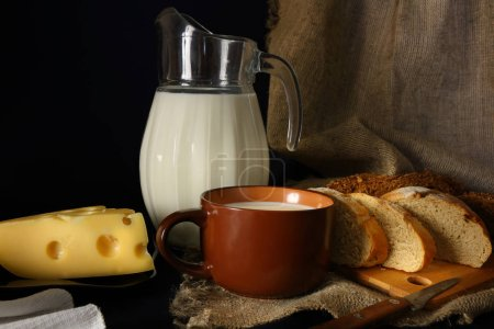 Still life with a jug of milk, cheese and bread on a burlap in a rustic style