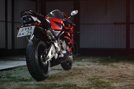 Photo for KRASNOYARSK, RUSSIA - September 27, 2019: Red and black sportbike Honda CBR 600 RR 2005 PC37 on the track at night. Light effect. - Royalty Free Image