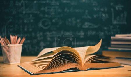 Photo pour Livres ouverts avec des formules sur le tableau concept .education - image libre de droit