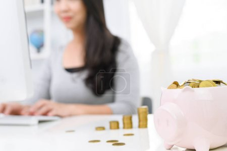 Foto de Linda alcancía con moneda de oro y borroso Mujer que trabaja en la computadora en el fondo de la oficina en casa. .. concepto de ahorro de dinero para la contabilidad financiera - Imagen libre de derechos