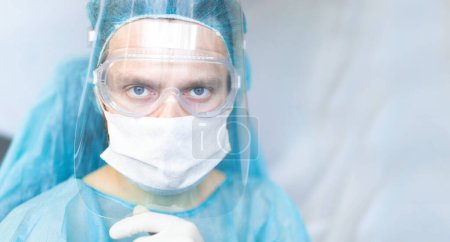 Photo for Surgeon with glasses and a protective shield and mask. Young specialist works in the operating room - Royalty Free Image