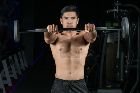 Photo for Muscular builder man training his body with barbell in Modern fitness center - Royalty Free Image