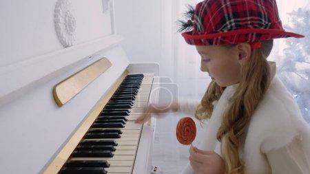 Photo pour Grandhomme au chapeau rouge jouant de la musique au piano et tenir la sucette dans la main. Adolescent fille joyeuse apprendre à jouer de la musique au piano. Sourire de mélodie de Noël jeu fille - image libre de droit