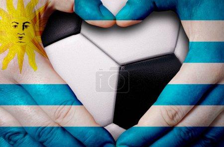 Photo pour Mains peintes avec un drapeau de l'Uruguay formant un cœur sur fond de ballon de football - image libre de droit