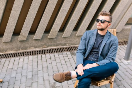 Photo for Handsome guy is sitting on chair outdoor on concrete wall background. He wears gray jacket, jeans, sunglasses. - Royalty Free Image