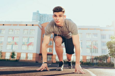Photo for Strong handsome guy in the morning on stadium. He wears sport clothes, listening to music through headphones, has preparation on start. - Royalty Free Image