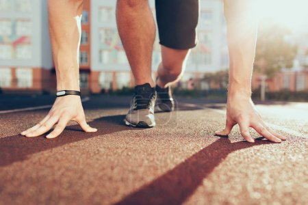 Photo for Muscle, hands, sunlight, legs in sneakers of strong guy on stadium in the morning. He has preparation on start. - Royalty Free Image