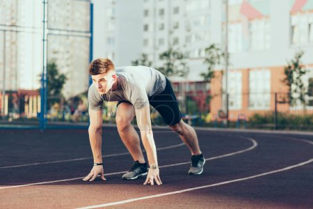 Photo for Young handsome guy in the morning on stadium. He wears sport clothes, listening to music through headphones, going to run. - Royalty Free Image