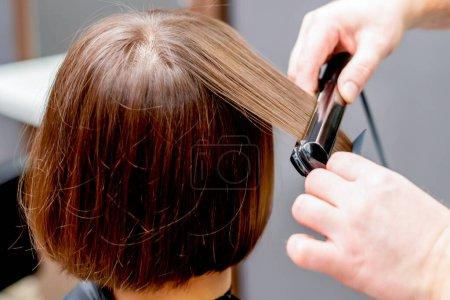 Photo pour Mains de coiffeur redresser les cheveux de la femme dans le studio de coiffure . - image libre de droit