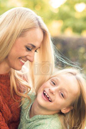 Photo for Beautiful young caucasian mother and little daughter smiling together on the green grass in the Autumn Park - Royalty Free Image