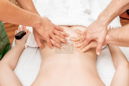 Photo for Woman receiving back massage with four hands of two male therapists close up. - Royalty Free Image