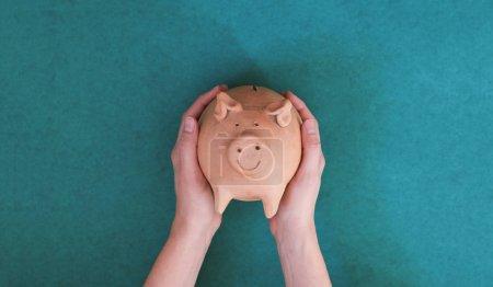 Photo pour Pièce de porc interagissant avec les mains féminines sur fond vert - image libre de droit