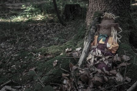 Photo pour Épouvantail avec une branche d'arbre à côté, assis entre les racines d'un vieil arbre, couvert de feuilles séchées, dans une forêt sombre. Contexte pour Halloween . - image libre de droit