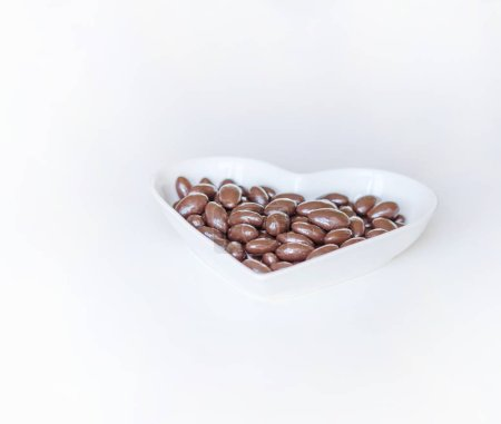 Photo for Nuts arranged in heart shape on background. Food image close up candy, chocolate milk, extra dark almond nuts. Love Texture on white grey table top view - Royalty Free Image
