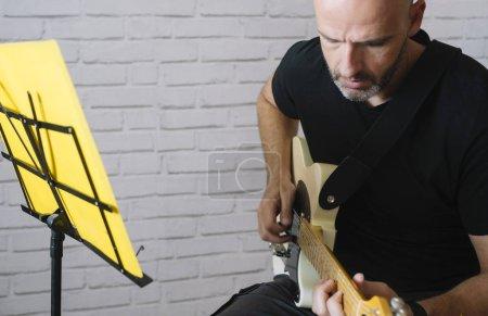 Photo pour Homme étudiant la musique avec guitare électrique à la maison - image libre de droit