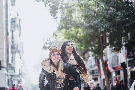 Photo pour Séduisante jeune couple lesbien dans la rue de la ville de Madrid - image libre de droit