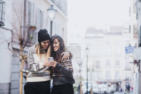 Photo for Two women with smartphone in the street - Royalty Free Image