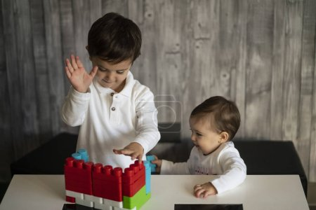 Photo for Two happy baby playing with toy blocks. - Royalty Free Image